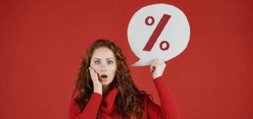 Mulher surpresa segura balão grafado o simbolo de porcentagem. Cor da roupa, fundo e simboli: Vermelho.